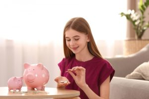 Teen girl counting the money from her piggy bank; financial tips for teens.