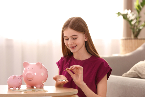 Teen girl counting her money from her piggy bank; financial tips for teens.